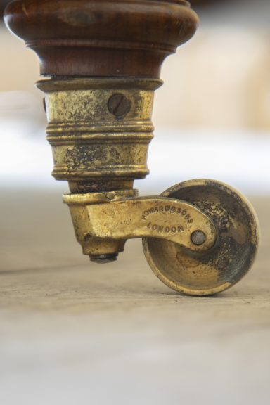 Image of the casters at the feet of a Howard & Sons piece of furniture, showing the original marking which says 'Howard & Sons London'